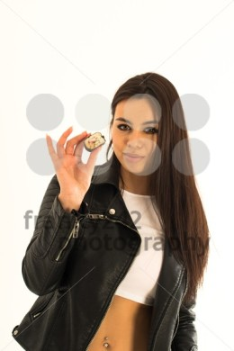 Attractive young woman holding sushi in her hand