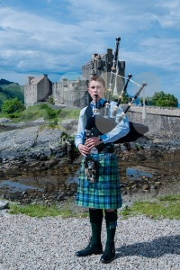 Bagpipe player in front of famous Eilean Donan Castle in the highlands of Scotland - franky242 photography