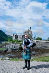 Bagpipe player in front of famous Eilean Donan Castle in the highlands of Scotland with great blue sky background - franky242 photography