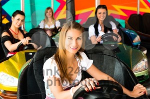 Beautiful girls in an electric bumper car in amusement park - franky242 photography
