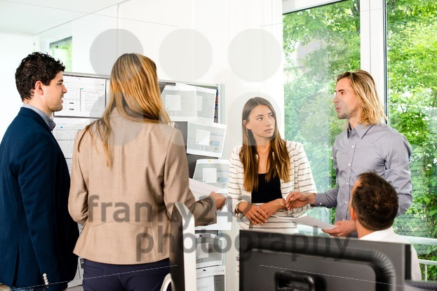 Businesspeople looking at bulletin board in office - franky242 photography