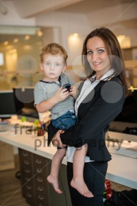 Businesswoman with small child in the office - franky242 photography