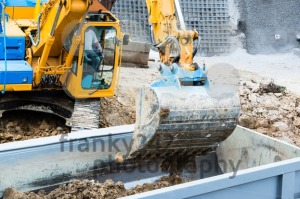 Closeup of excavator filling a dump truck - franky242 photography