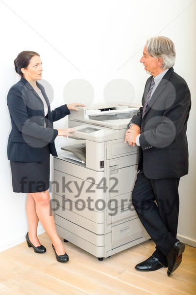 Colleagues talking at  copying machine in the office - franky242 photography