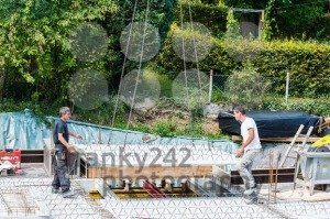 Crane lifting part of a cement floor with workers adjusting - franky242 photography