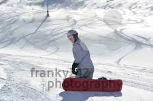 Female snowboarder kneeling in powder snow - franky242 photography