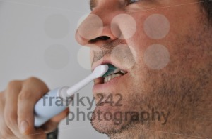 Man brushing his teeth with electric toothbrush - franky242 photography