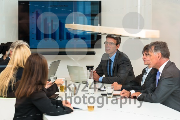Mixed group in business meeting seen through glass door - franky242 photography