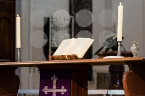 Open Bible and candles on the altar of a church - franky242 photography