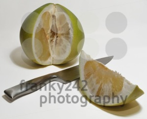 Pummelo-with-cut-out-slice-and-knife-on-white