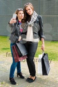 Two attractive girls making a selfie after shopping - franky242 photography