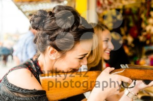Two attractive girls playing shooting games at German funfair - franky242 photography