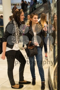 Two attractive young women looking through shop window in a mall - franky242 photography