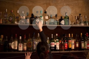 Waitress and bar shelves full of alcoholic beverages bottles - franky242 photography