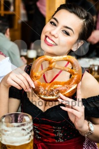 Woman in Dirndl eating Oktoberfest Pretzel - franky242 photography