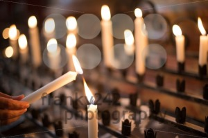 Woman lighting prayer candle - franky242 photography