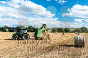 tractor throwing out hay roll - franky242 photography