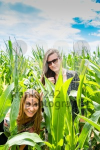 Two young girls hiding in a green cornfield - franky242 photography