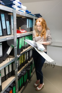 attractive businesswoman searching file in company archives - franky242 photography