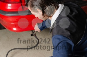 Mechanic measuring exhausts of a car in garage - franky242 photography