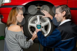 Auto mechanic and female trainee changing a car tyre in garage - franky242 photography