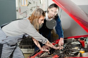 Auto mechanic guiding a female trainee in garage - franky242 photography