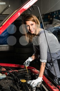 Young female trainee fixing car engine in garage - franky242 photography
