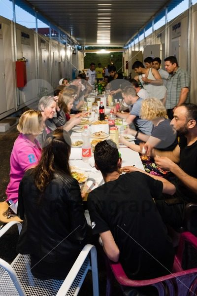 Muslim refugees and German volunteers sit together eating dinner during Ramadan fasting month - franky242 photography