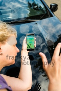Pedestrian being hit by car while playing Pokemon Go on her smartphone - franky242 photography