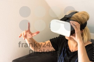 Woman resting on sofa wearing VR headset glasses - franky242 photography