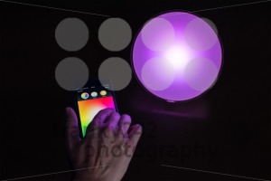 Female hand using Apple iPhone to control a Philips Hue smart home light - franky242 photography