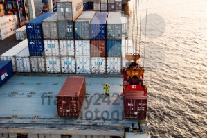 worker assisting container uploading at dock - franky242 photography