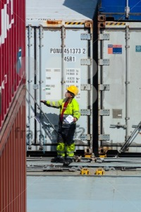 worker supervising container uploading at dock - franky242 photography