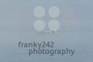 Container ship passing an offshore windpark during fog - franky242 photography