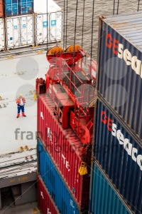 worker supervising container uploading at dock of a container ship - franky242 photography