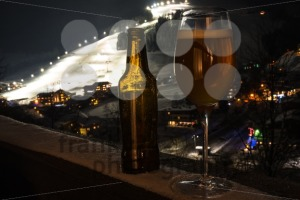 Glass and bottle with craft beer on a balcony at skiing village - franky242 photography