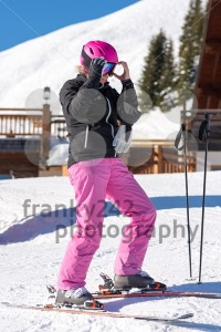 Female skier getting dressed in front of skiing hut - franky242 photography