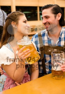 Young couple flirting in Oktoberfest beer tent - franky242 photography