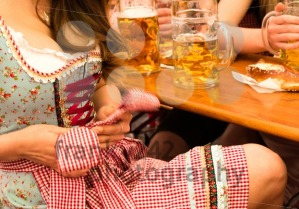 Beautiful young woman fixing her Dirndl at Munich Oktoberfest - franky242 photography