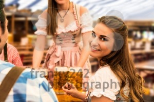 Waitress delivers beers in tent with happy visitors in a beer tent at Munich Oktoberfest - franky242 photography