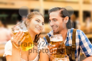 Young couple flirting in Oktoberfest beer tent while drinking beer - franky242 photography