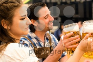 Young couple toasting in Oktoberfest beer tent - franky242 photography