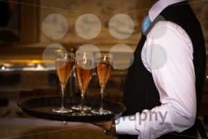 Male waiter welcomes guests with sparkling wine - franky242 photography