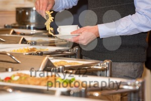 man picking food from chafing dish heaters - franky242 photography