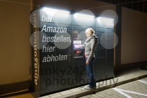 A woman is using an Amazon Locker station located next to an Aldi supermarket. - franky242 photography