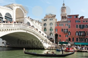 Famous Ponte di Rialto with traditional gondola passing in Venice, Italy - franky242 photography