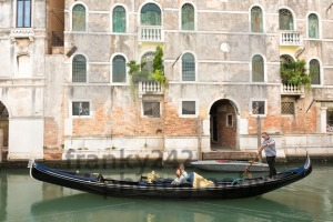 Venetian gondolier punting gondola through green canal waters of Venice, Italy - franky242 photography