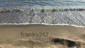 Waves crashing gently on quiet sandy beach - franky242 photography