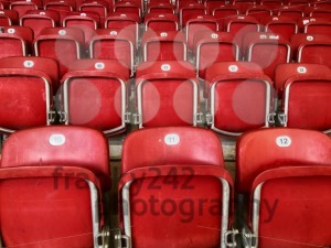 Empty red plastic seats in a stadium - franky242 photography
