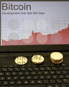 Bitcoins and rising chart on laptop computer - franky242 photography